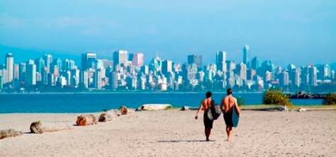 Two surfers walking on beach in Vancouver Canada.